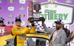 Kyle Busch, front left, holds his trophy presented to him by Nashville Superspeedway President Erik Moses, front right, after winning a NASCAR Xfinity
