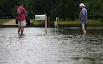 Danny Gonzales, right, stands in front of his flooded house with his neighbor Bob Neal in Slidell, La., Saturday, June 19, 2021.