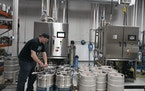 Lead operator Adam Schill works on the mostly alcohol-free beer, which is being put in kegs from a machine that separates alcohol from a brewed beer a