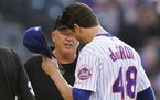 Third base umpire Ron Kulpa, left, looks inside the cap of New York Mets starting pitcher Jacob deGrom (48) on Monday.