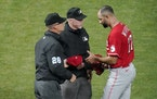 Cincinnati Reds' relief pitcher Art Warren (77) gets a glove and cap check for sticky substances from umpires Tuesday night at Target Field.