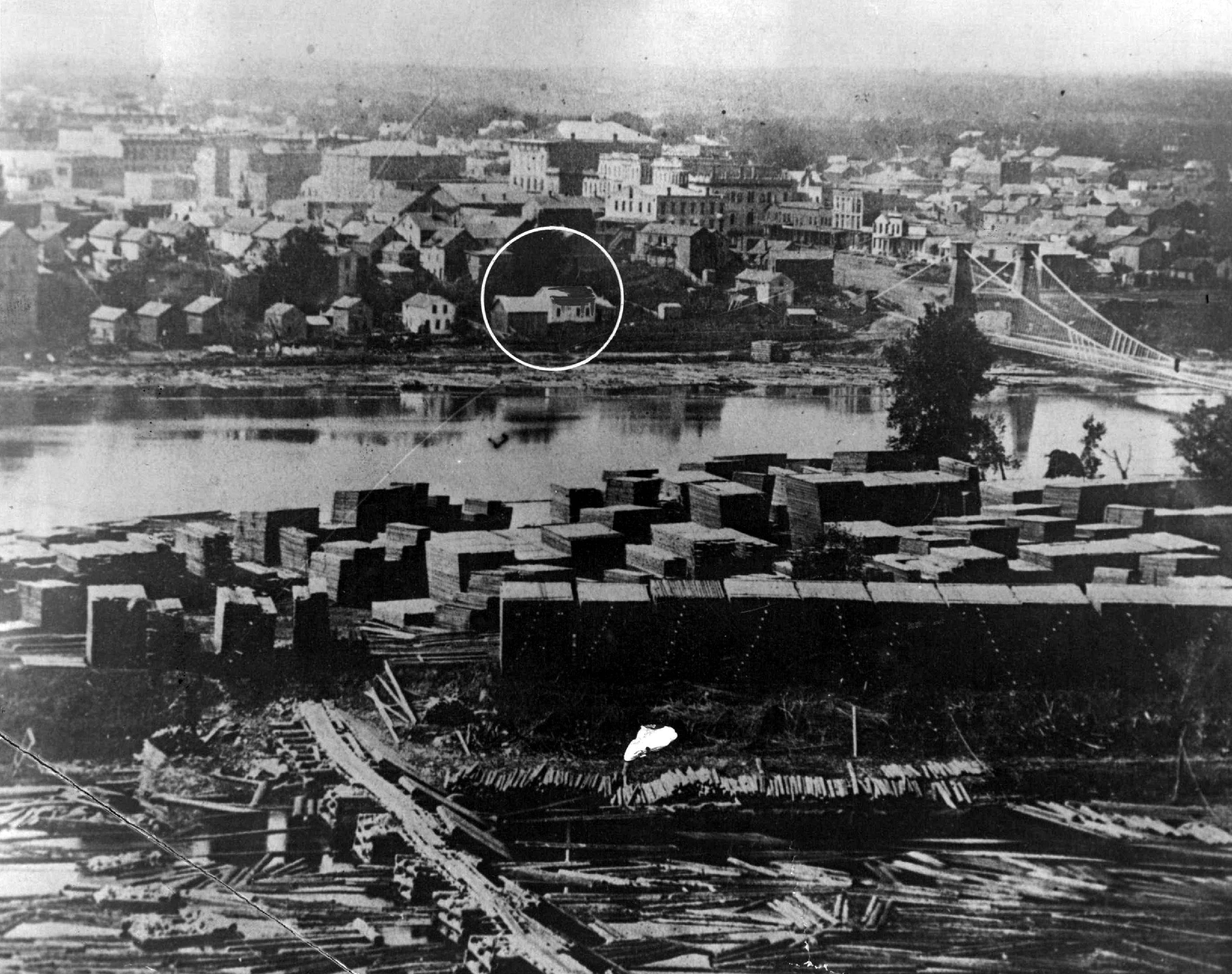 This 19th Century photo of downtown Minneapolis shows the Stevens House in its original location alongside the Mississippi River.