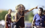 Maia Peterson of Stewartville, right, helped an exhausted Elle Kuechel of Eden Valley Watkins off the track after she collapsed at the finish line.