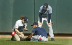 Byron Buxton holds his ankle after he stumbled during an intrasquad game last July. Manager Rocco Baldelli, left, spoke with him be before he left the