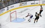 Canadiens center Nick Suzuki shoots an empty net goal ahead of Vegas center William Karlsson
