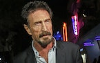 FILE — In this Dec. 12, 2012, file photo, anti-virus software founder John McAfee answers questions to reporters as he walks on Ocean Drive, in the