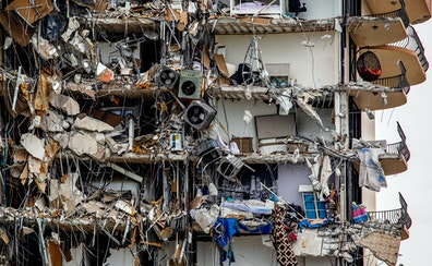 Air conditioning units and personal belongings hang from a high-rise residential building that is partially collapsed in Surfside, Fla.
