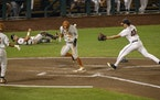 Texas' Eric Kennedy ran home on a wild pitch by Virginia pitcher Mike Vasil (48) during the Longhorns' 6-2 victory over Virginia in the College Wo