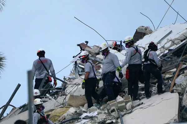 Rescue workers look through the rubble where a wing of a 12-story beachfront condo building collapsed, Thursday in the Surfside area of Miami.