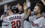 Minnesota Twins' Eddie Rosario is greeted in the dugout after his two-run home run during the third inning of a baseball game against the Detroit Tige