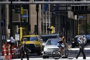 At top, a pedestrian navigates a skyway Tuesday in downtown Minneapolis. Above, cars and people fill the streets near the Hennepin County Government C