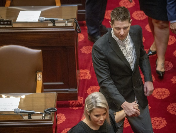 Waseca police officer Arik Matson was guided his wife, Megan Matson, as they made their way to the Senate chambers to be recognized Tuesday.
