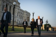 Gov. Tim Walz, with his wife, Gwen, walked the signed education budget law over to the office of Secretary of State Steve Simon on Wednesday.