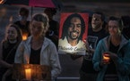 Adrian Perryman, of St. Paul, gathered with family and friends at Larpenteur Avenue and Fry Street for a candlelight vigil in remembrance of Philando