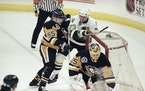 Minnesota North Stars' Brian Bellows (23) knocks the goal net off its post after he was sent crashing into it by Pittsburgh Penguins' Larry Murphy (55