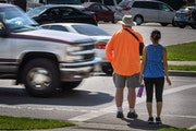 A maroon and silver truck drove through the marked crosswalk in front of pedestrian volunteers Dave Passiuk and Nelsie Yang on St. Paul's East Side