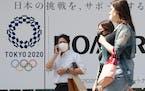 People walk past an Tokyo Olympics logo in Tokyo, on June 25.