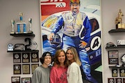 Ayden, Kristi and Alyssa Copham, in front of painting of their late husband & father Jed.