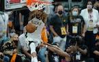 Milwaukee Bucks forward Giannis Antetokounmpo, top, dunks over Phoenix Suns guard Chris Paul during the second half of Game 5 of basketball's NBA Fina