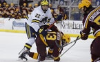 Michigan's Owen Power watched the puck while working against the Gophers' Cullen Munson in December. Power, a 6-6 defenseman, is considered the to