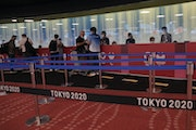 People arriving for the 2020 Summer Olympics wait for their credentials to be validated before they can leave Haneda Airport in Tokyo on Monday.