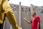 Dave Gatzmer has installed more than 90 phones on a noise barrier as part of a guerrilla art project in St. Louis Park.