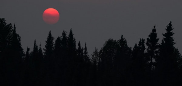 Wildfire smoke from Canada's Quetico Provincial Park caused a haze in the air as the sun set over Seagull Lake in the Boundary Waters Canoe Area Wil