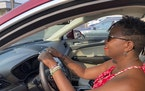 Jessica Pitts sits behind the wheel of a 2019 Lincoln MKC on the lot of Jack Demmer Lincoln in Dearborn, Mich., on Monday, July 19, 2021. Pitts bought