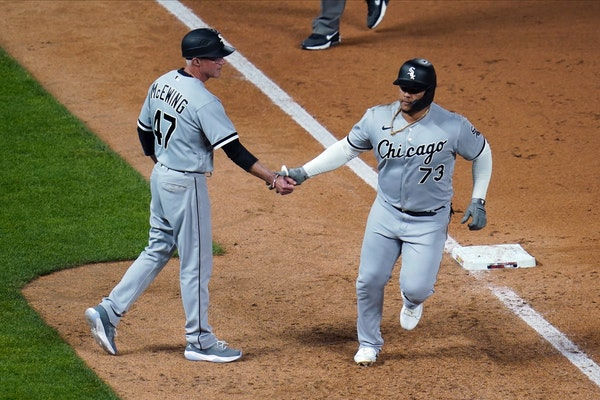 Chicago White Sox's Yermin Mercedes, right, is congratulated by third base coach Joe McEwing after his home run off Minnesota Twins' Willians Astu