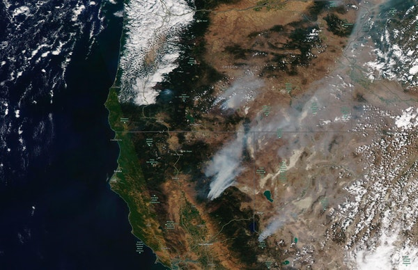 This satellite image shows the wildfires in Northern California and Oregon on Wednesday, July 21, 2021.