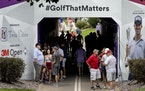 Fans gathered in a tunnel during a weather delay during the first round of the 3M Open in Blaine.