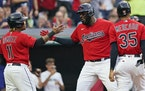Cleveland Indians' Franmil Reyes, center, is congratulated by Jose Ramirez and Oscar Mercado after hitting a three-run home run in the third inning