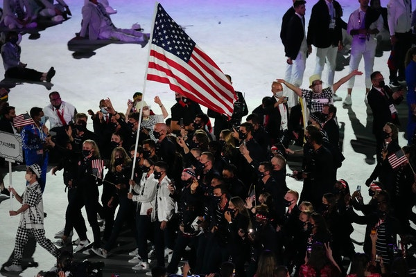 Sue Bird and Eddy Alvares carried the U.S. flag during the opening ceremony at Olympic Stadium in Tokyo.