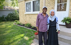 """St. Cloud residents Youssouf """"Joe"""" Omar and Hamdia Mohamed stand by a duplex they own as part of their business, Victory Plus Housing."""