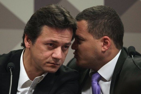 Wesley Batista, an executive at the world's largest meatpacker JBS, listens to his lawyer Ticiano Figueiredo, during his testimony at the Parliament
