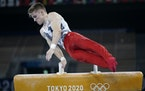 Shane Wiskus performs on the pommel horse Saturday during the men's gymnastic qualifications.