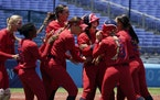 Amanda Chidester, center, is mobbed by her American teammates after her walkoff, two-run single in the eighth inning beat Australia on Sunday in the O