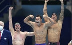 United States men's 4x100m freestyle relay team members Bowe Becker, Blake Pieroni, and Caeleb Dressel reacted after winning the gold medal Monday.
