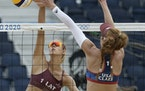 Kelly Claes, right, of the United States and Tina Graudina of Latvia battled at the net during a women's beach volleyball match at the Tokhyo Olympi