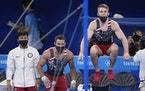 Gymnasts from the United States, from left, Yul Moldauer, Samuel Mikulak, and Shane Wiskus watch teammate Brody Malone performing on the horizontal ba