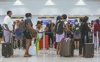 Mask-wearing travelers queue at Miami International Airport, June 23, 2021.