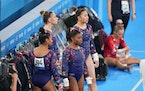 Jordan Chiles, with her back turned away from camera, Simone Biles, center, Grace McCallum and Sunisa Lee, of the United States, wait on the side duri