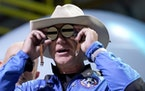 Jeff Bezos, founder of Amazon and space tourism company Blue Origin, puts goggles over his eyes that belonged to aviator Amelia Mary Earhart during a