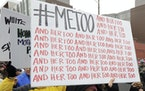 In this Jan. 20, 2018 file photo, a marcher carries a sign with the popular Twitter hashtag #MeToo used by people speaking out against sexual harassme