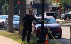 A St. Paul Police officer gathered up crime scene tape in the Mac-Groveland neighborhood on Monday after a man was found shot in a vehicle. He later d