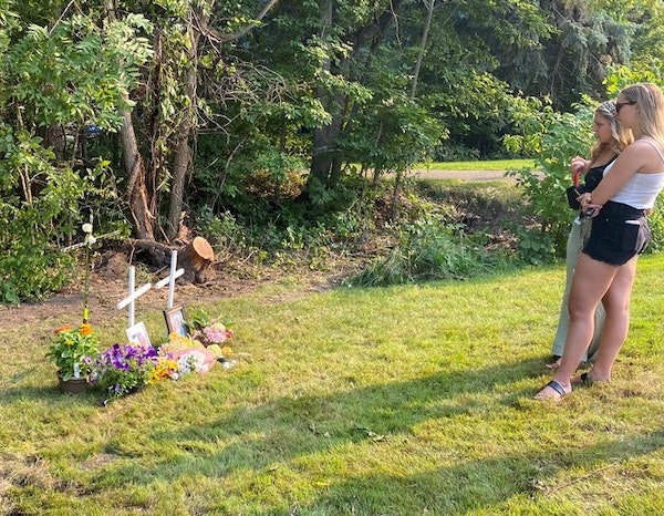 Mourners stopped by the memorial for Mack Motzko and Sam Schuneman along a busy North Shore Drive on Monday, July 26, leaving golf balls and hockey pu