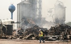 Salvage crews and volunteer firefighters cleaned up the charred pile that was the Clinton Grain Elevator on Monday morning.