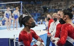Simone Biles talked to teammate Suni Lee during the artistic gymnastics women's final Tuesday in Tokyo.