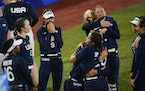 Members of team United States react after losing to Japan in the gold medal softball game.