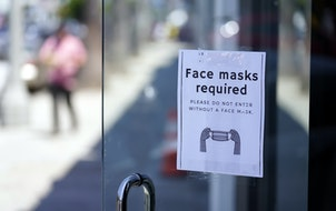 A sign advises shoppers to wear masks outside of a store in Los Angeles. Los Angeles County reinstated an indoor mask mandate due to rising COVID-19 c